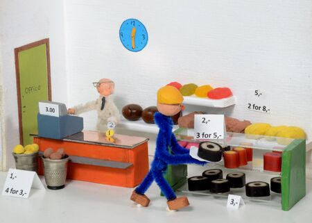 Model setup situation that illustrates how a customer buys goods in a shop, pays and goes with his cake..