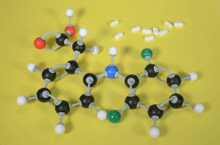 Molecule model of Diclofenac, the active ingredient in many pain killers. White is Hydrogen, black is Carbon, red is Oxygen, green is Chlorine and blue is Nitrogen. Stockfoto