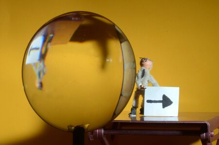 Little figurine holds a sign with an arrow, a convex lens shows him upside down. Stockfoto