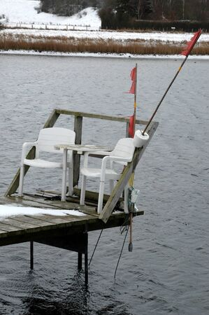Small jetty with two chairs for a cosy time, all covered with snow Stockfoto - 148858453