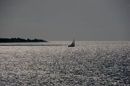 Small boat in backlight on a shining ocean with a peninsula in the background.