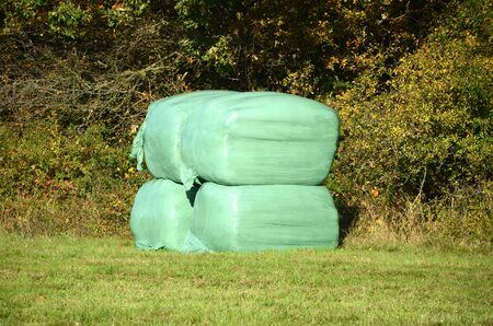Small pile with silage bags on a field.