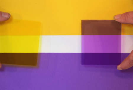 Color filters held against a sheet of paper with two complementary colors. As can be seen each filter filters the opposite color to become quite dark. Stockfoto - 150572180
