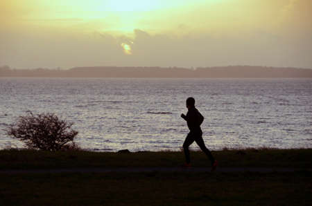 Silhouette of a person jogging in evening light, with the sea as background.