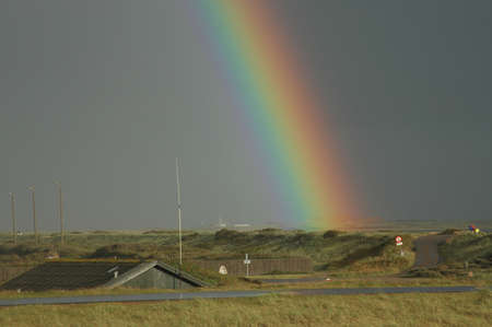 The end of the rainbow. A rainbow seems to hit the ground in the flat land. Stockfoto
