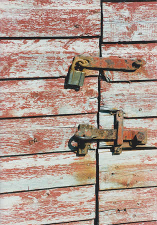 Rugged red shed gate locked with rusty lock and fittings. Stockfoto