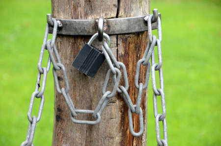 Padlock with chains on a wooden pole. Stockfoto