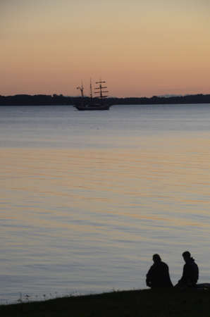 Old sail ship passes out on the sea while two persons in silhouette watch