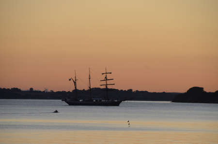 Old sail ship goes to port on a calm sea in evening light. Stockfoto