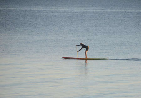 Calm sea with a person rowing a surfboard.