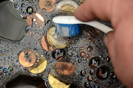 Black Euro coins being washed, suggesting the term