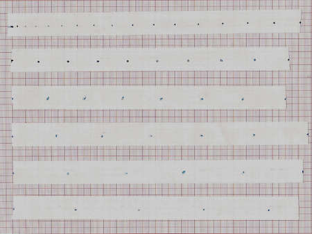 Paper strip from motion timer having recorded a free fall attached to millimeter paper. THe strip is cut in the mittle of a dot so that full continuity is maintained. The timer places 100 dots per second.