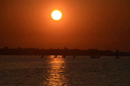 Sunset over the sea, optimist dinghys are seen as silhouettes Stockfoto - 157104395