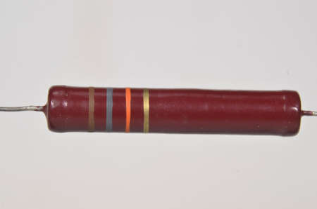 Closeup on single electronic resistor. Color bands tell us that the reistance of this component is 18kOhm with a tolerene of 5%