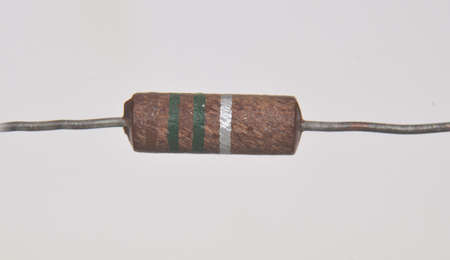 Closeup on single electronic resistor. Color bands tell us that the reistance of this component is 1.500.000 Ohms or 1,5 MOhm with a tolerence of 10% Stockfoto - 157767568
