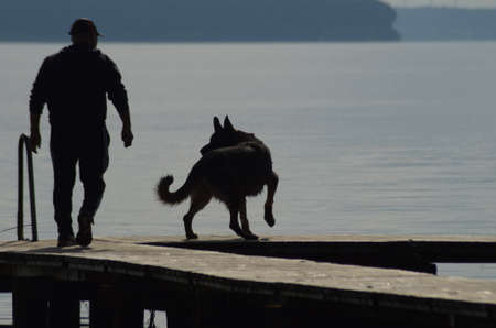 Silhouette of person and german shepherd dog on a woden bridge with water in the background.