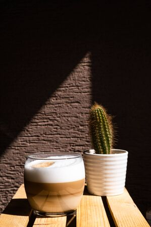 Coffee latte in a glass on direct sunlight