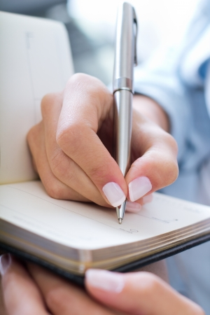 close up image: young woman taking notes at home  Stock Photo