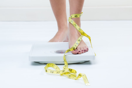 A picture of female feet standing on a bathroom scales and a tape measure