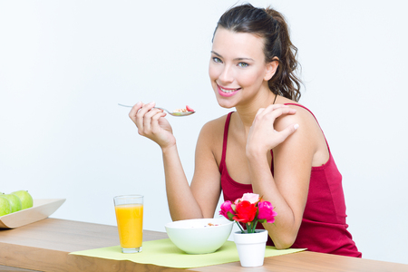 having breakfast: pretty young woman having breakfast at home