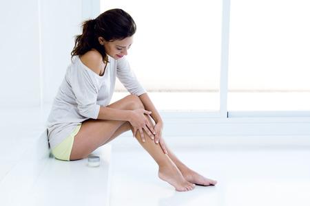 mujer celulitis: Cuidado del cuerpo. Mujer que aplica la crema en las piernas