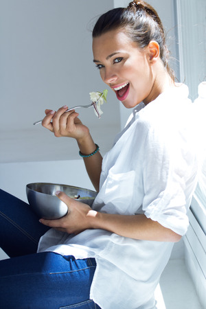 beautiful woman eating salad at home Stock Photo