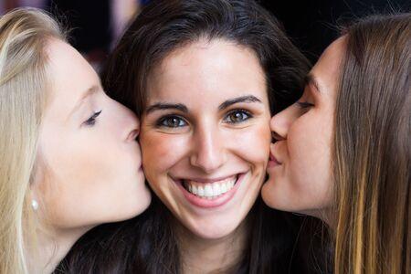 かわいい笑顔の女の子の肖像画は彼女の友人によって頬にキスをしました。