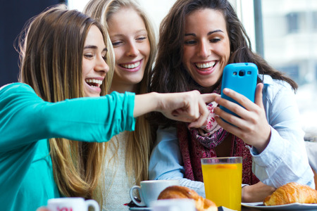 girl friends: A group of friends having fun with smartphones Stock Photo