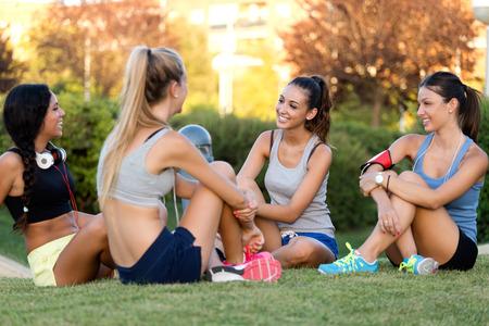 chicas adolescentes: Retrato al aire libre de correr muchachas que se divierten en el parque con el teléfono móvil.