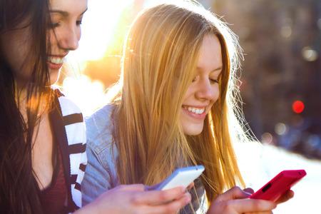 gente feliz: Un grupo de amigos charlando con sus teléfonos inteligentes en la calle