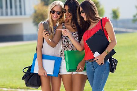 Retrato de tres chicas charlando con sus teléfonos inteligentes en el campus Foto de archivo - 43826385