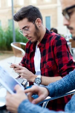 jovenes empresarios: Retrato al aire libre de dos jóvenes empresarios que trabajan en la cafetería. Foto de archivo