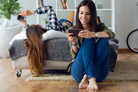 Portrait of two beautiful young woman using mobile phone at home.