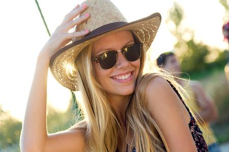 夏の日に帽子を持つ若い魅力的な女性の屋外のポートレート。