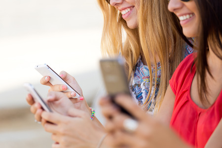 Portrait of three girls chatting with their smartphones at the campus Stockfoto
