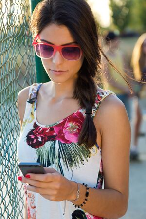 ethnicity: Outdoor portrait of young beautiful girl texting with her phone.