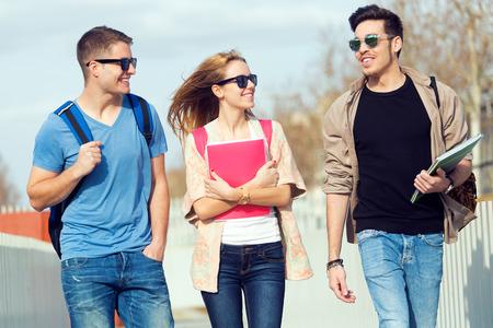 men talking: Portrait of a group of friends talking in the street after class.