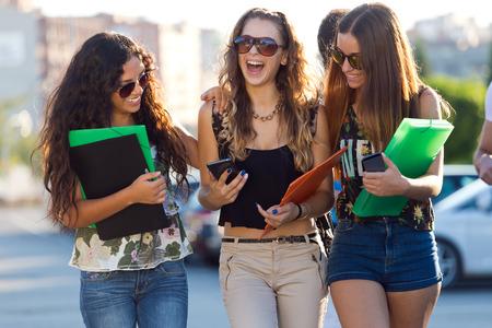jovenes estudiantes: Retrato de un grupo de amigos hablando en la calle después de las clases