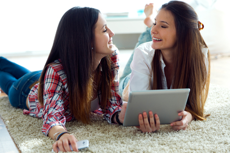 digital tablet: Portrait of two beautiful young woman friends using digital tablet at home.