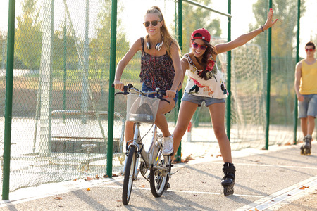 Outdoor portrait of group of friends with roller skates and bike riding in the park.