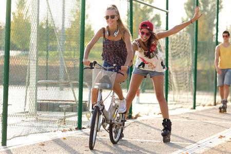 patín: Retrato al aire libre de un grupo de amigos con los patines y bicicleta en el parque.