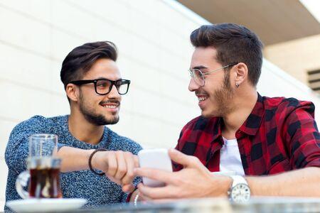 jovenes empresarios: Retrato al aire libre de dos j�venes empresarios que trabajan en la cafeter�a. Foto de archivo