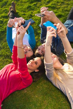 公園でスマート フォンで写真を撮る友人のグループの屋外のポートレート