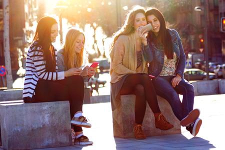 通信: A group of friends having fun with smartphones in the street