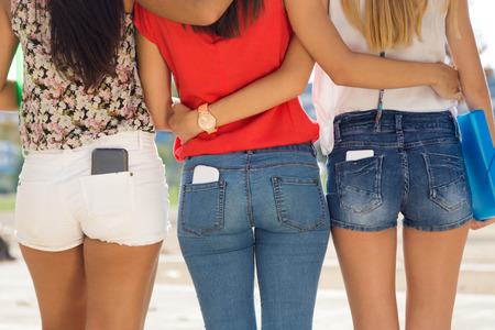 Portrait of three students girls with mobile in the pocket.