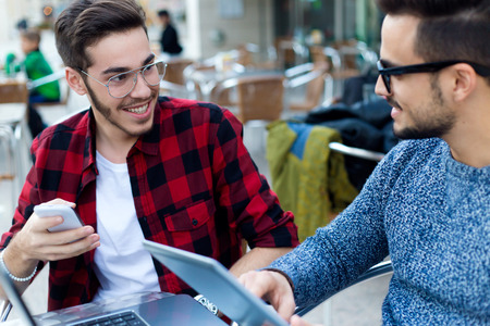 young entrepreneurs: Outdoor portrait of two young entrepreneurs working at coffee shop. Stock Photo