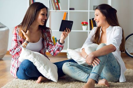 sitting on floor: Portrait of two beautiful young woman friends using digital tablet at home.