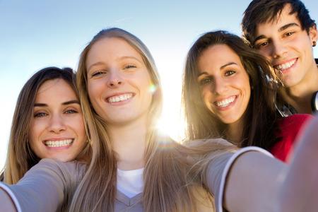 Retrato al aire libre de un grupo de amigos que toman fotos con un teléfono inteligente en la calle Foto de archivo - 43826664