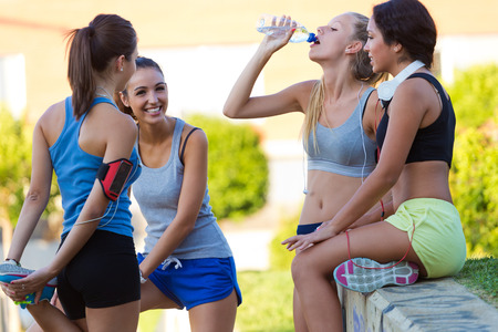 gimnasio mujeres: Retrato al aire libre de un grupo de jóvenes mujeres que realizan estiramientos en el parque.