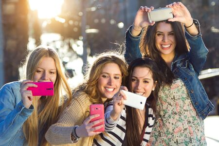 Outdoor portrait of group of friends taking photos with a smartphone in the street
